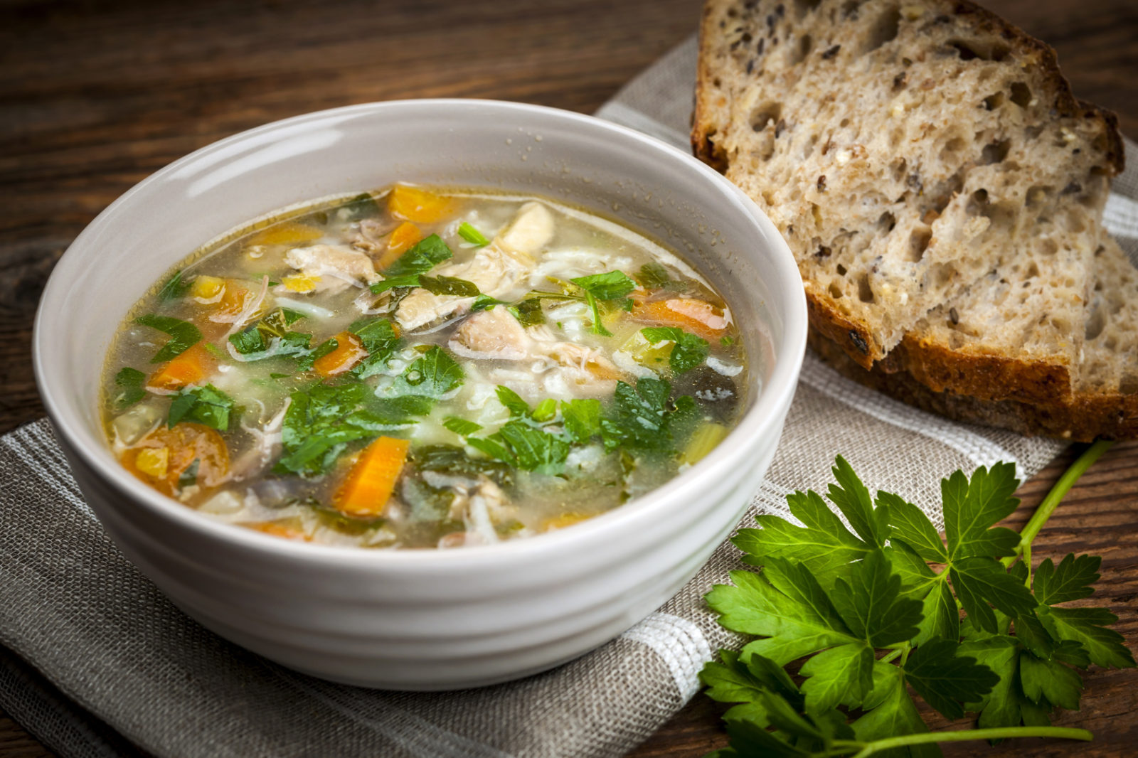 Clear Hatteras clam chowder with vegetables and herbs and a piece of bread on a rustic table
